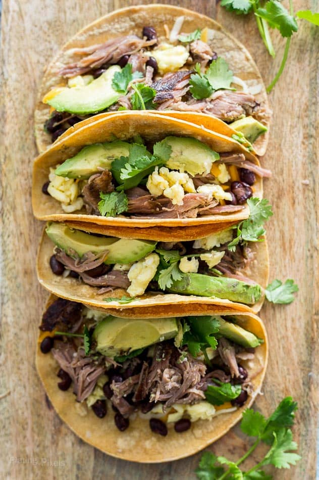 Slow Cooker Carnitas Breakfast Tacos stacked together on a wooden surface topped with avocado and cilantro