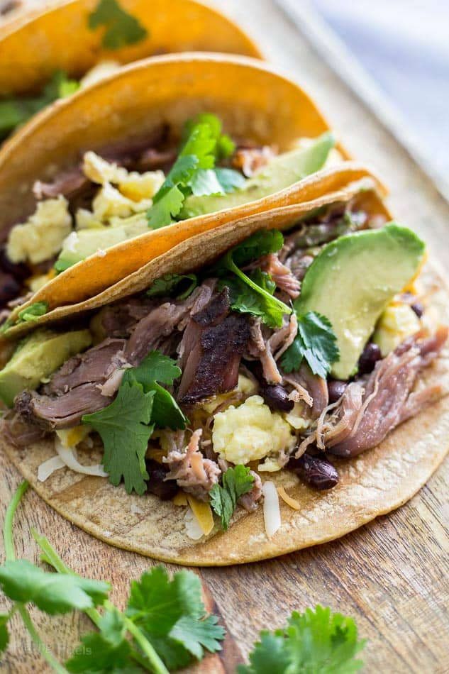 A close up of Carnitas Breakfast Tacos on a wooden surface with sliced avocado