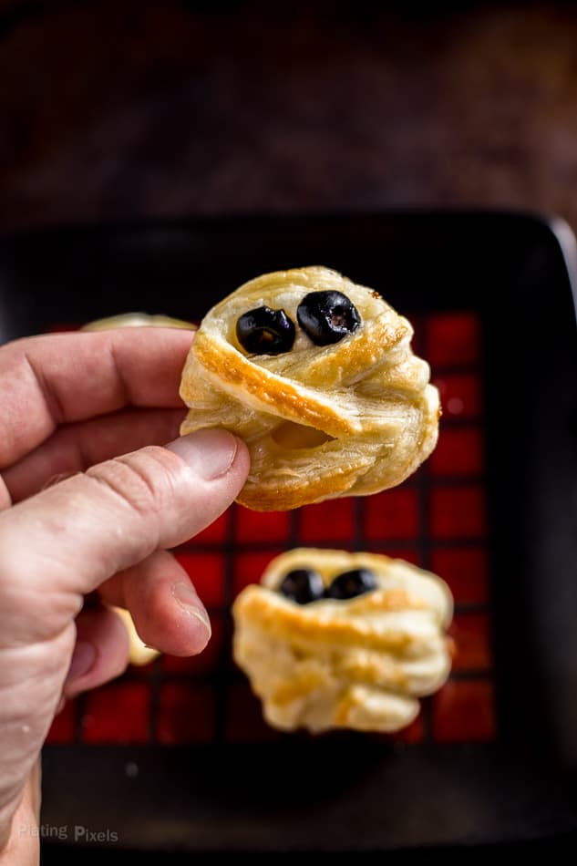 Hand holding just baked Halloween Puff Pastry Mummy Cheese Wheel