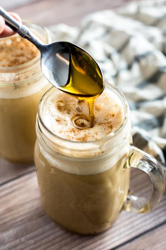 Drizzling caramel sauce into a homemade pumpkin spice latte