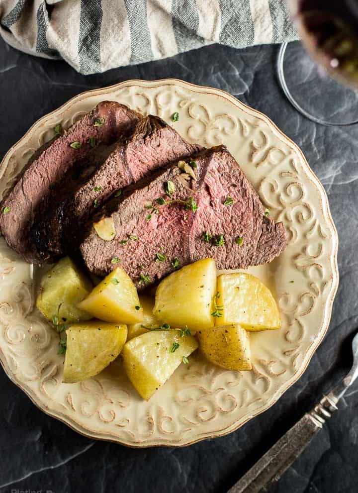 Sliced Red Wine Marinated Prime Rib served with Potatoes on a cream colored plate next to glass of red wine