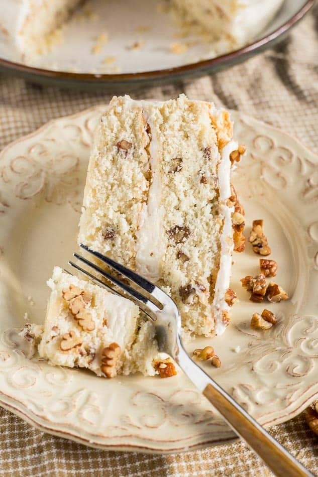 A close up of a fork cutting into a slice of Butter Pecan Cake with Buttercream Frosting