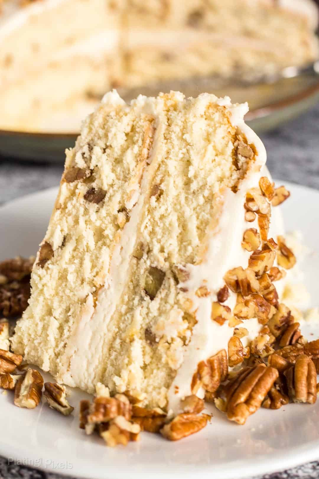 A close up of a slice of Butter Pecan Cake on a plate garnished with chopped pecans