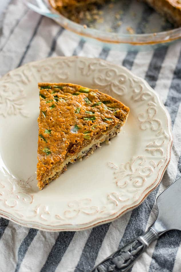 Slice of Chorizo and Cheddar Quiche with Quinoa Crust on a plate
