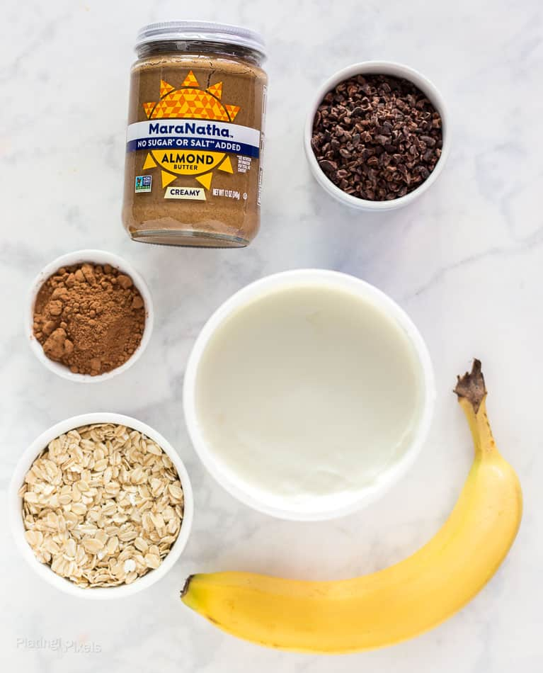 All ingredients to make Chocolate Almond Butter Breakfast Parfaits laid out on a marble table