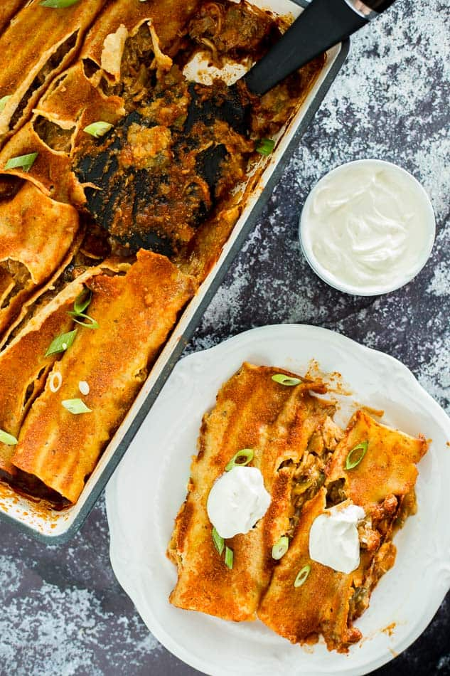 Using a spatula to serve Slow Cooker Carnitas Enchiladas on a plate topped with sour cream