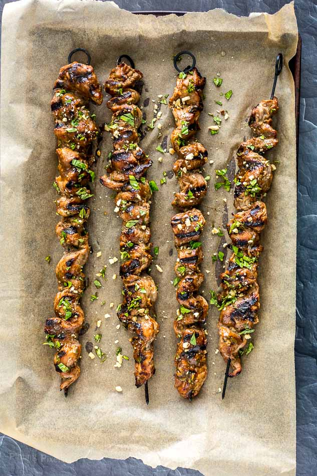Grilled Pork Satay Skewers on a sheet of parchment paper