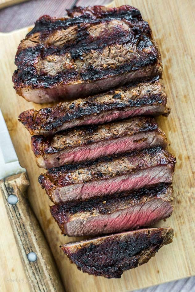 Grilled Ribeye Steak sliced and resting on a cutting board with knife next to it