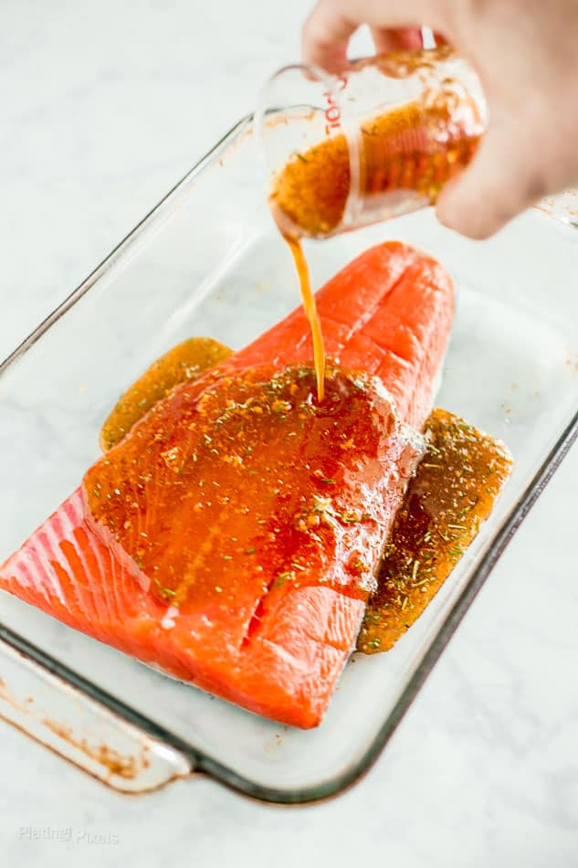 Process shot of drizzling maple glaze onto raw salmon fillet in a clear baking dish