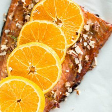 Close up of Maple Glazed Sheet Pan Salmon on baking sheet topped with orange slices