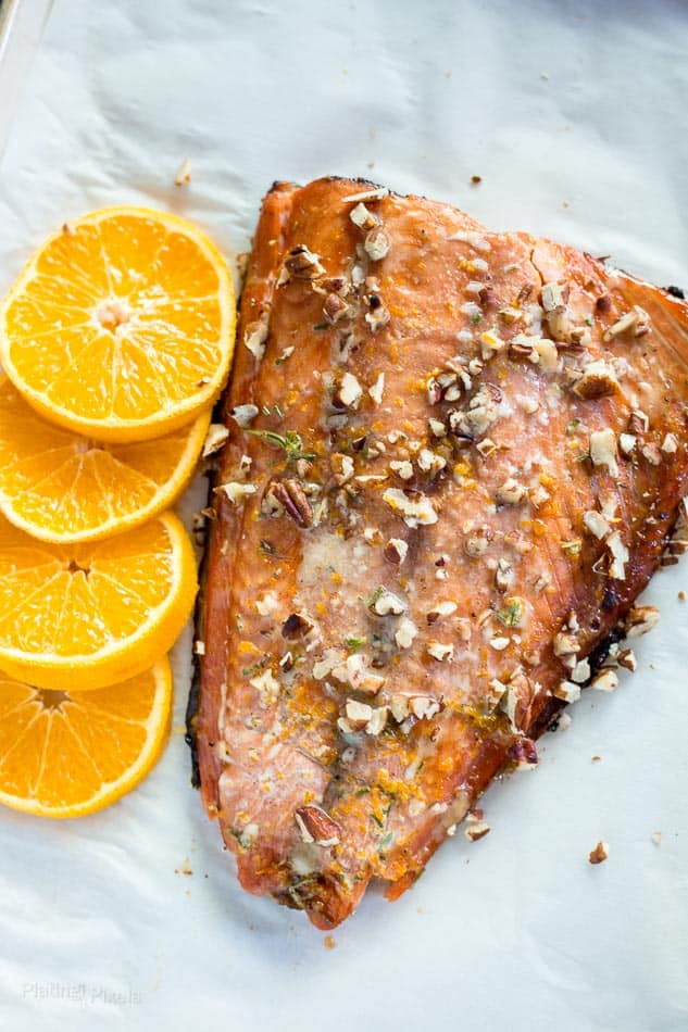 An overhead shot of just baked salmon with chopped pecans and slices of orange