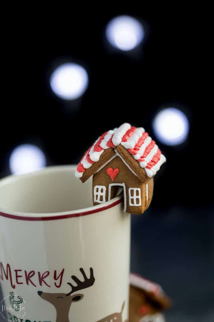 Mini decorated Gingerbread House cookie topper on edge of coffee mug