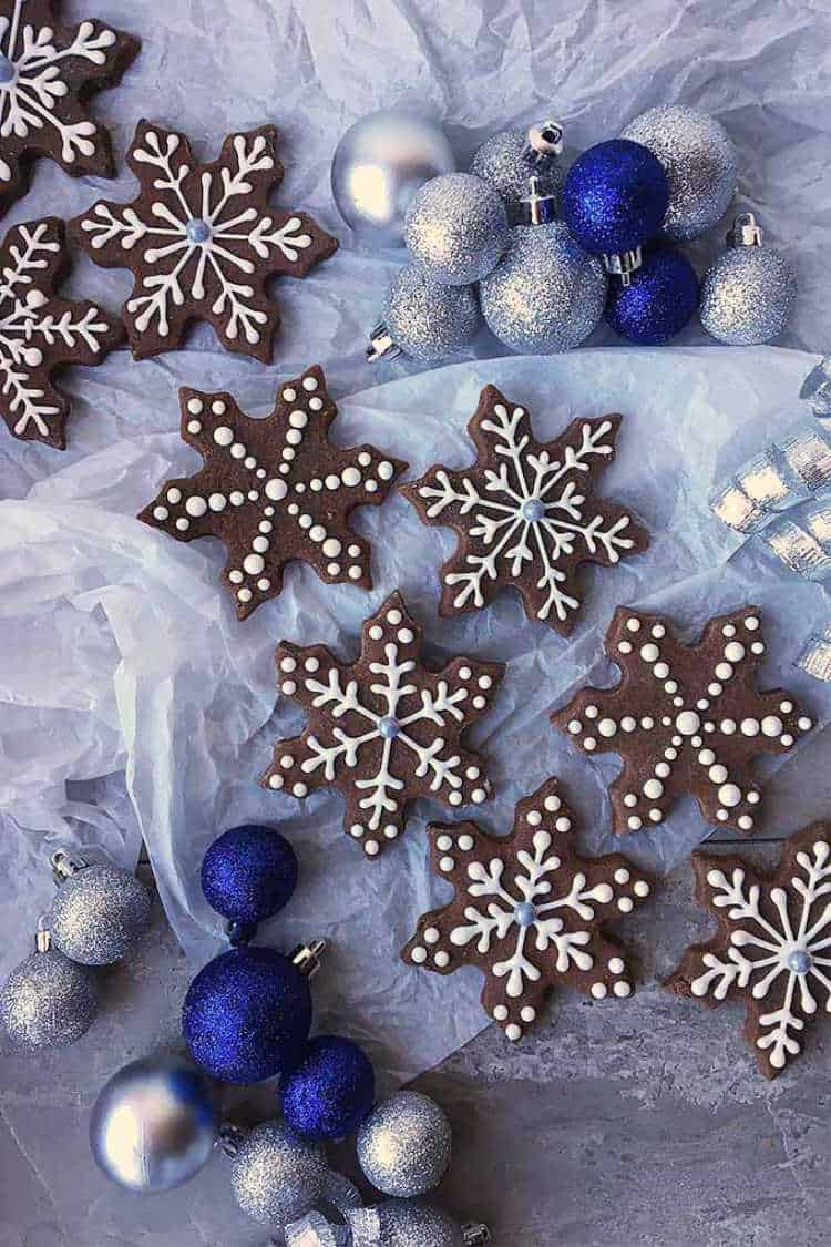 Overhead shot of Brownie Snowflake Cutout Cookies next to elegant ornaments