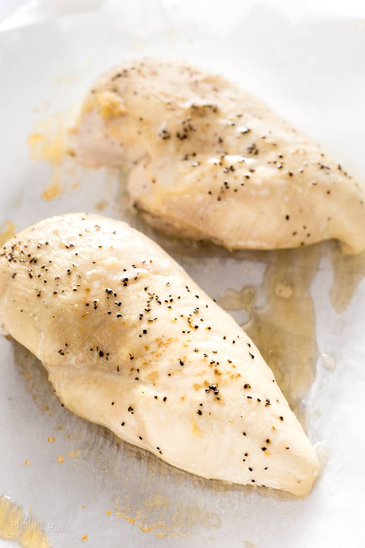 Two just baked chicken breasts over parchment paper in a baking dish