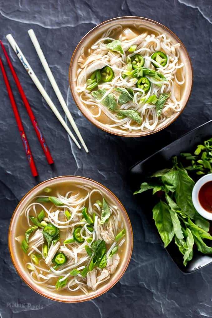 Two bowls of Slow Cooker Chicken Pho Soup on table ready to eat