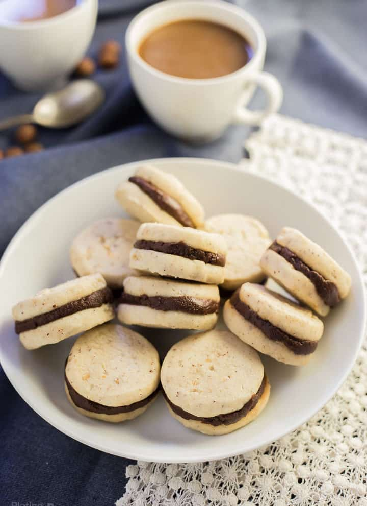 Pumpkin Spice Chocolate Shortbread Cookies sandwiches piled on a plate with coffee in background