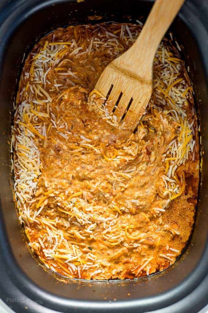 Wooden spoon stirring shredded cheese into queso dip base in a slow cooker