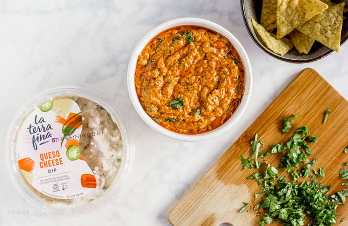 Overhead shot of Slow Cooker Chorizo Queso Dip in a bowl next to package or La Terra Fina dip