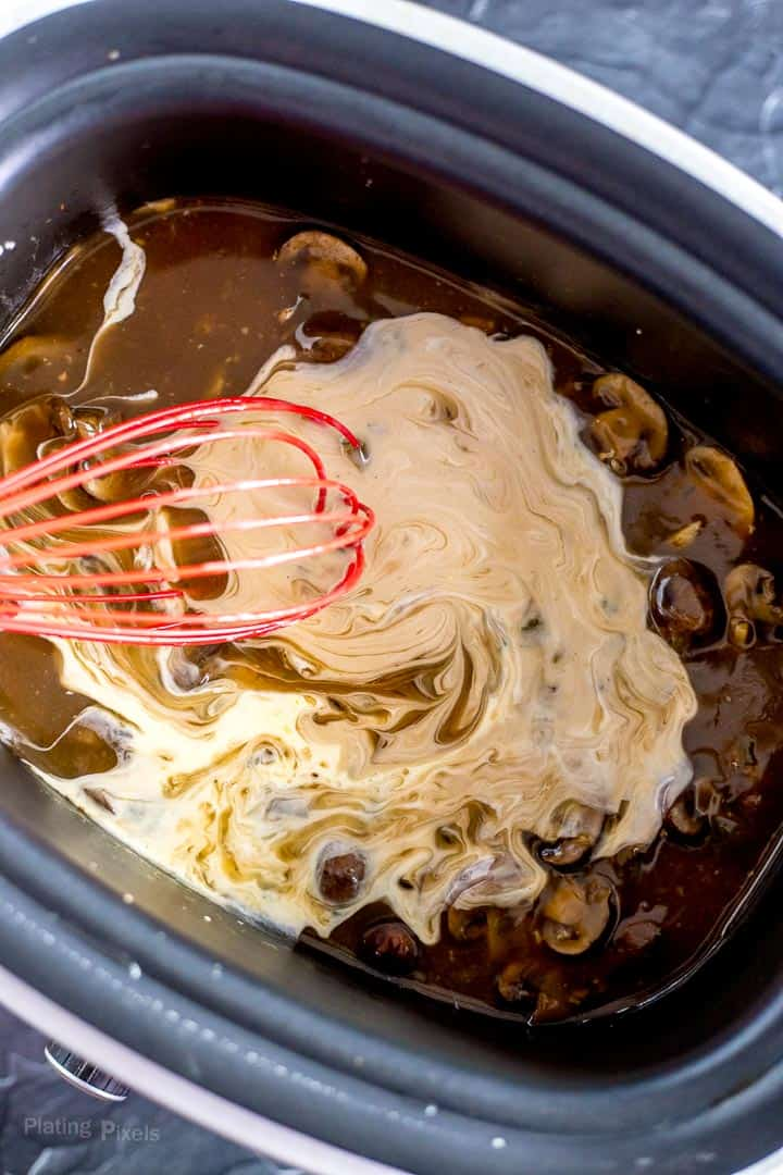 Stirring cream into marsala sauce with whisk in slow cooker