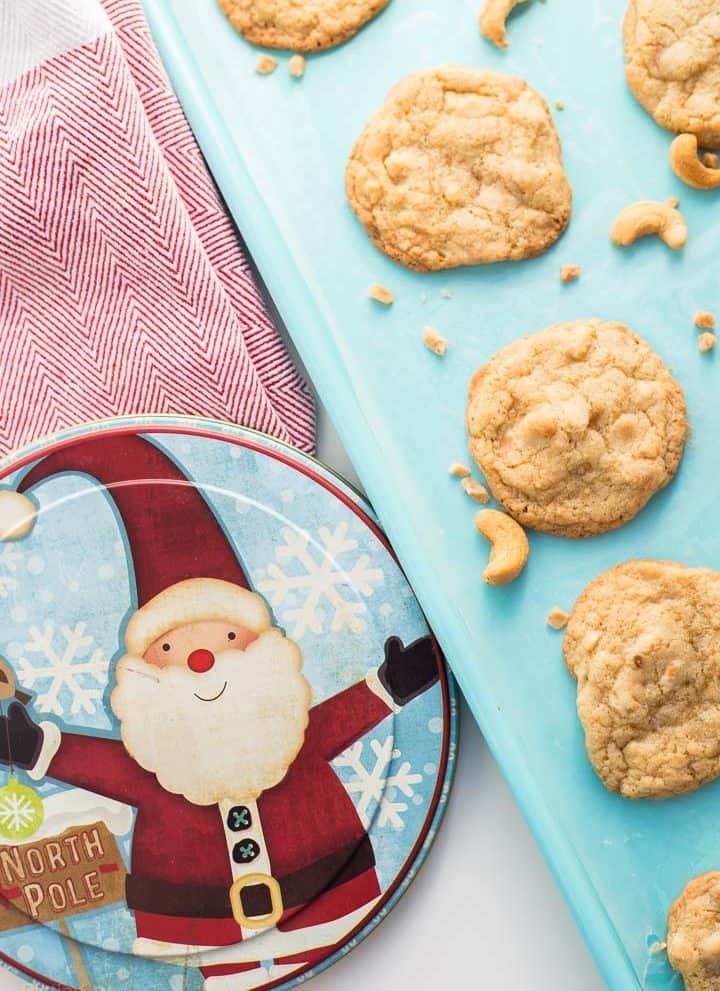 Chewy Cashew Toffee Cookies on teal cookie sheet with a santa decorated cookie tin beside it