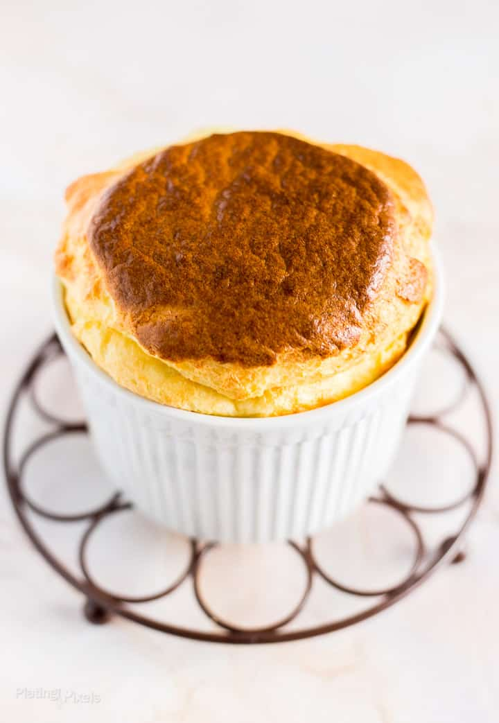 Angled shot of Easy Cheese Souffle with Brie Cheese sitting on cooling rack over white background