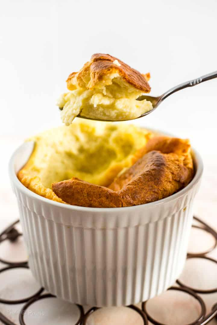A scoop of Easy Cheese Souffle on a spoon hovering over ramekin of cheese souffle