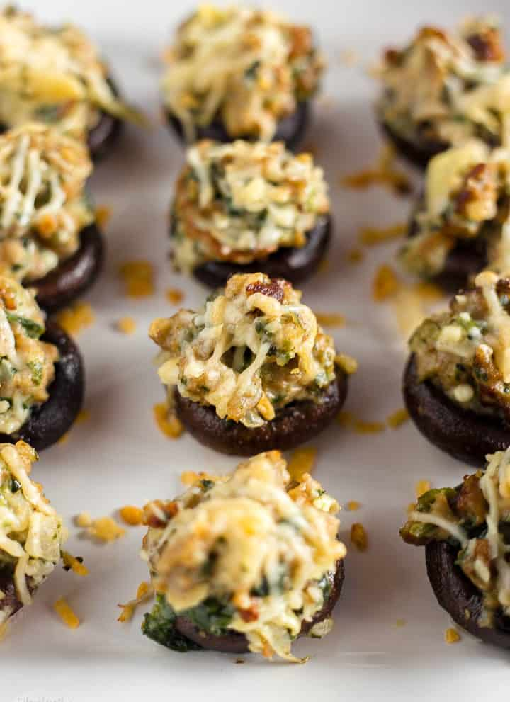 Close up shot of gluten-free Sausage Stuffed Mushrooms on a white plate ready to be served