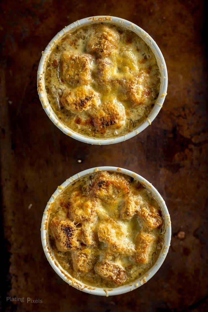 Overhead shot of two ramekins of French Onion Soup just broiled on a baking sheet