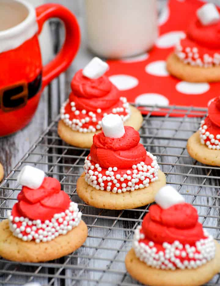 Santa hat frosted decorated Christmas cookies on wire baking sheet