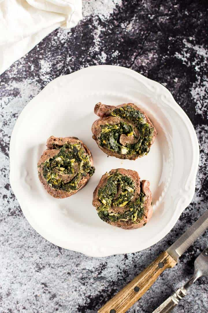 Overhead shot of three Creamy Spinach Stuffed Flank Steak Pinwheels on a plate