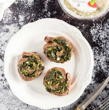 Three Creamy Spinach Stuffed Flank Steak Pinwheels on a plate next to container of La Terra Fina dip