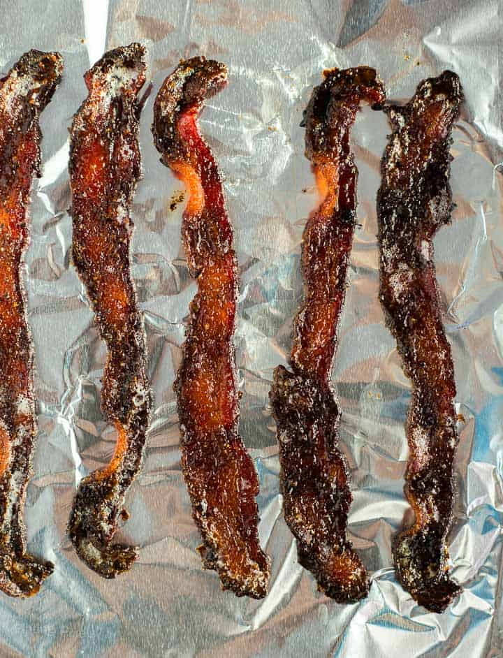 Cooked candied bacon pieces on a bacon sheet