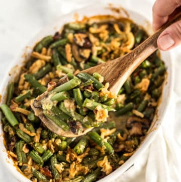 Hand scooping String Bean Casserole with Candied Bacon with a wooden serving spoon