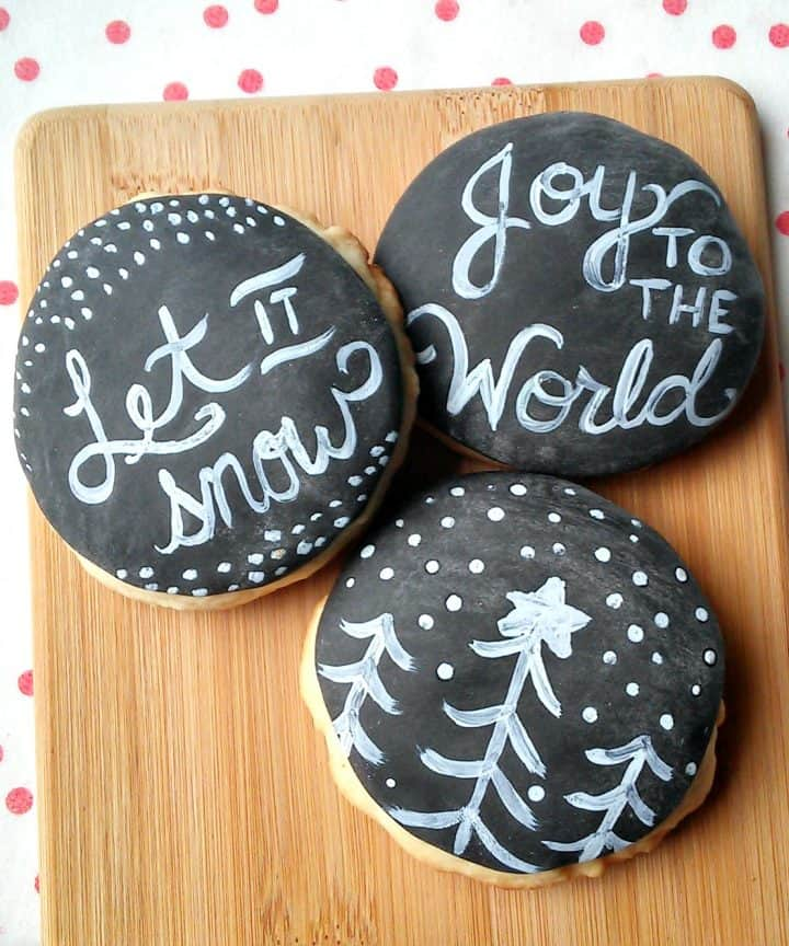 Three chalkboard frosted decorated Christmas cookies on wooden board