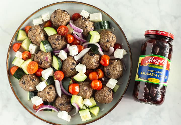 Plate of Greek Baked Meatballs and veggies next to a bottle of Mazzetta Kalamata olives