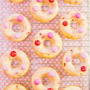 An overhead shot of Strawberry Glazed Baked Doughnuts on a cooling rack topped with pink M&M's