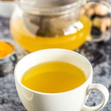 Cup of Turmeric Tea next to pot of more tea