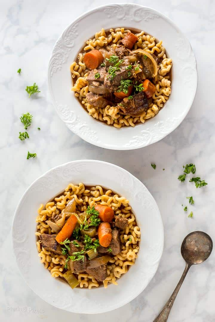 Two bowls of prepared Slow Cooker Beef Stew with root vegetables on a marble table