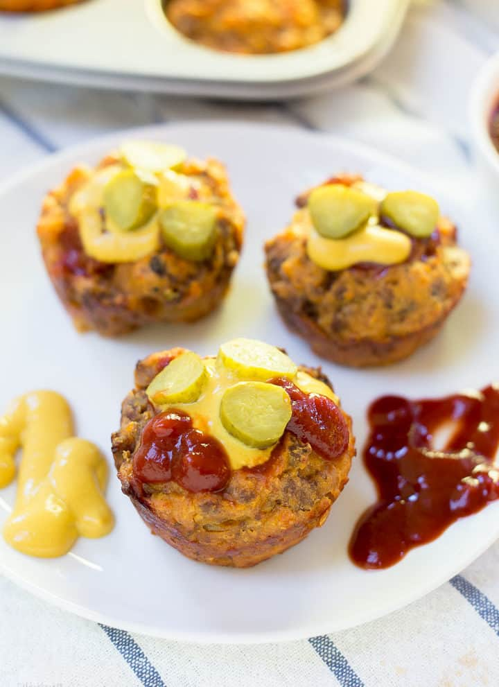 Mini Cheeseburger Muffins on a plate with pickles and ketchup