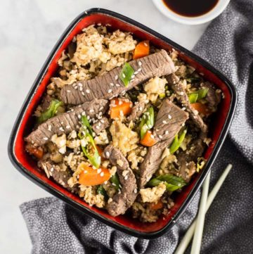 Overhead shot of Keto Beef Fried Rice in a bowl with chopsticks next to it