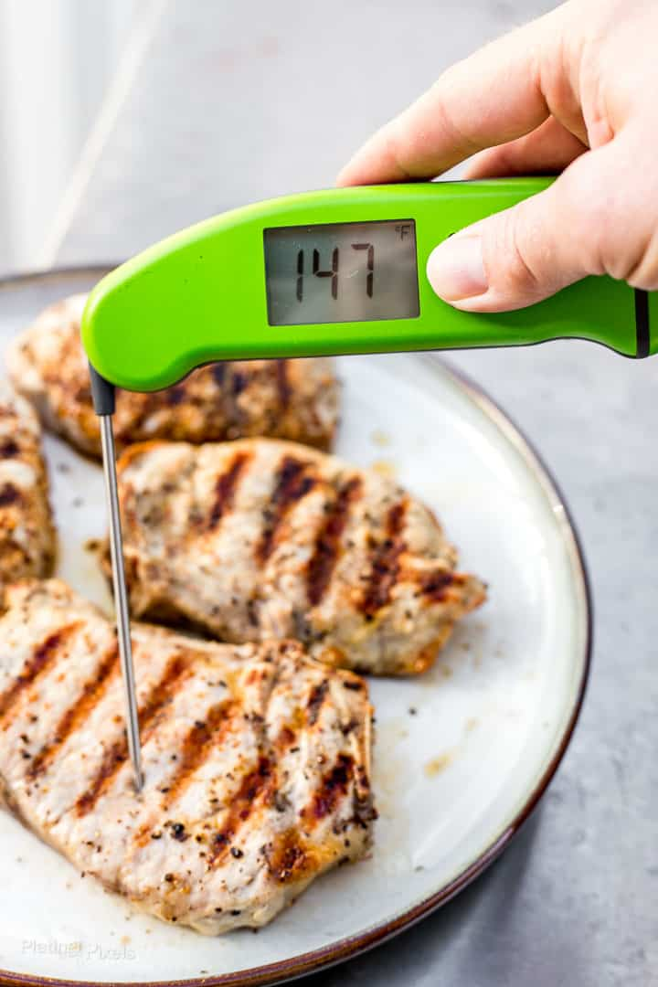 Checking temperature of grilled pork chops with a digital thermometer (temp is 147 degrees)