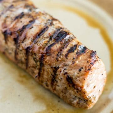 Grilled pork tenderloin resting on a plate