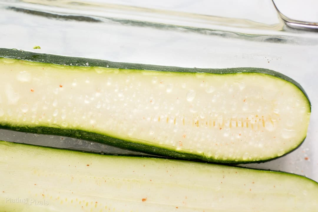 Close up of salting zucchini showing bead of water on the surface