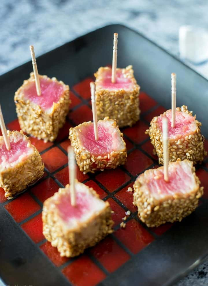 Seared Sesame Seared Ahi Tuna Bites on a black plate with toothpicks inserted in them