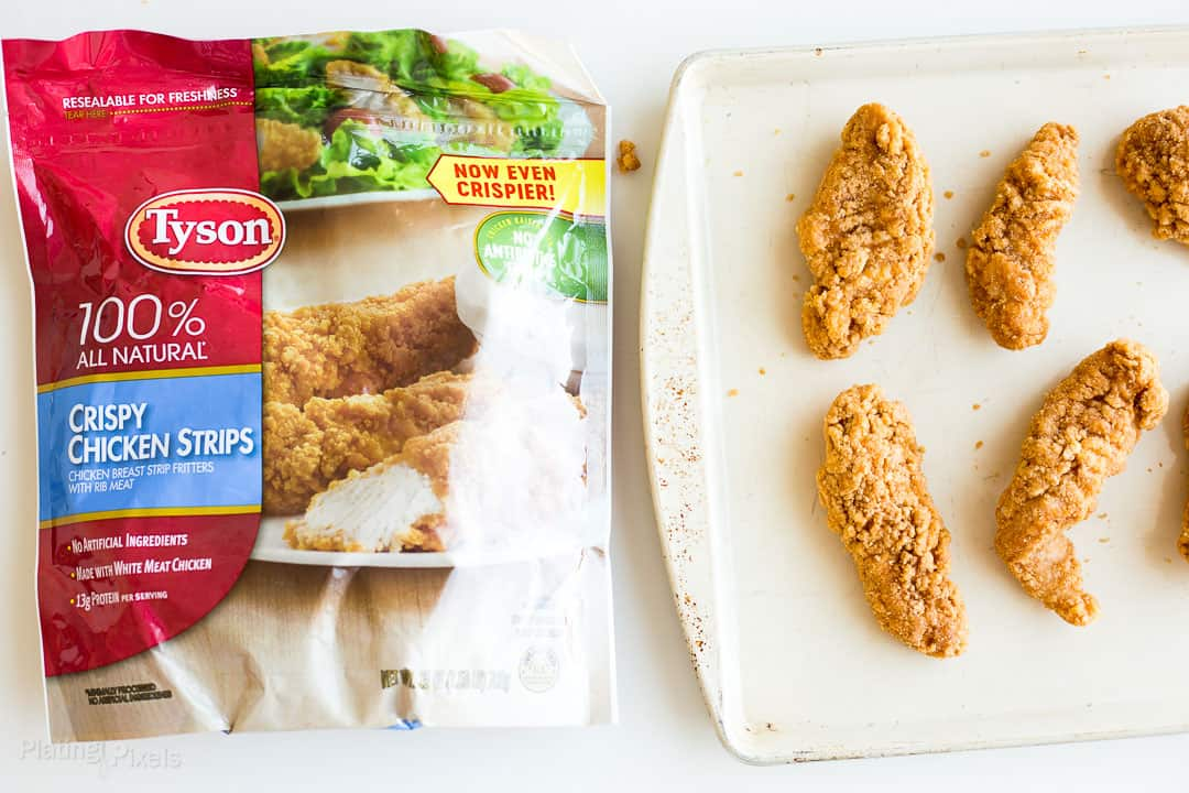 A package of Tyson® Crispy Chicken Strips next to chicken strips on a baking sheet