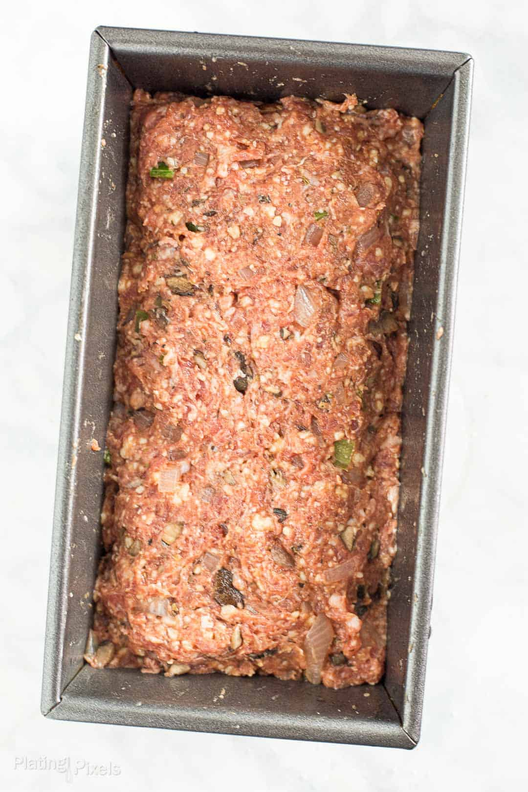 Prepared meatloaf mixture in a loaf pan ready to be baked