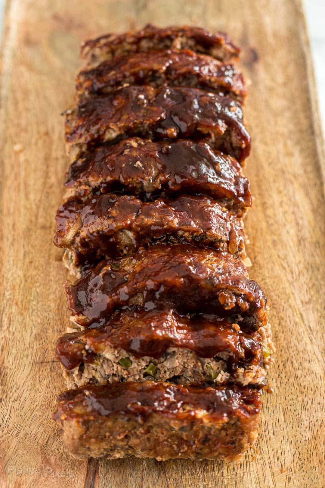 Slices of mushroom meatloaf covered in BBQ sauce on a cutting board