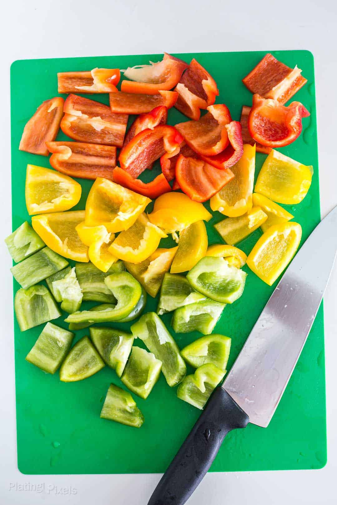 Process shot of chopped bell peppers on a cutting board