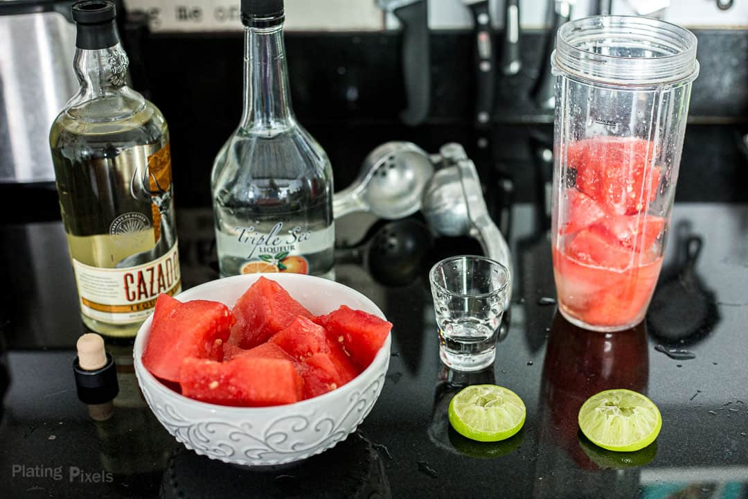 Ingredients needed to make a watermelon margarita prepped on a kitchen counter