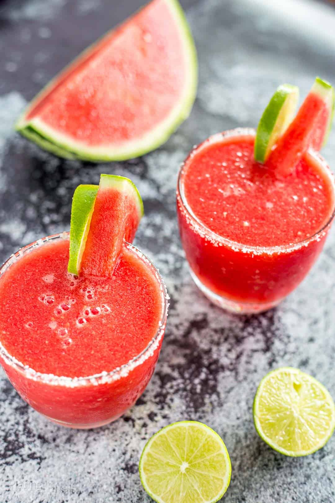 Two Frozen Watermelon Margaritas garnished with lime and watermelon wedges